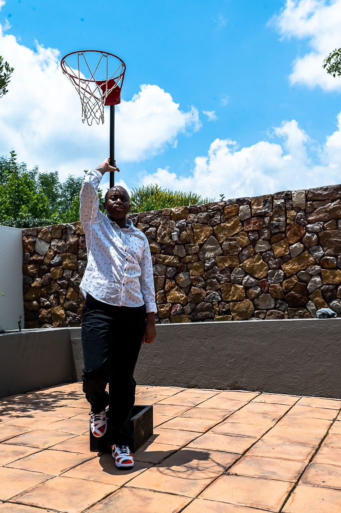 Picture of Zekwande standing next to a basketball hoop. Basketball is one of Zekwande's favourite sports.